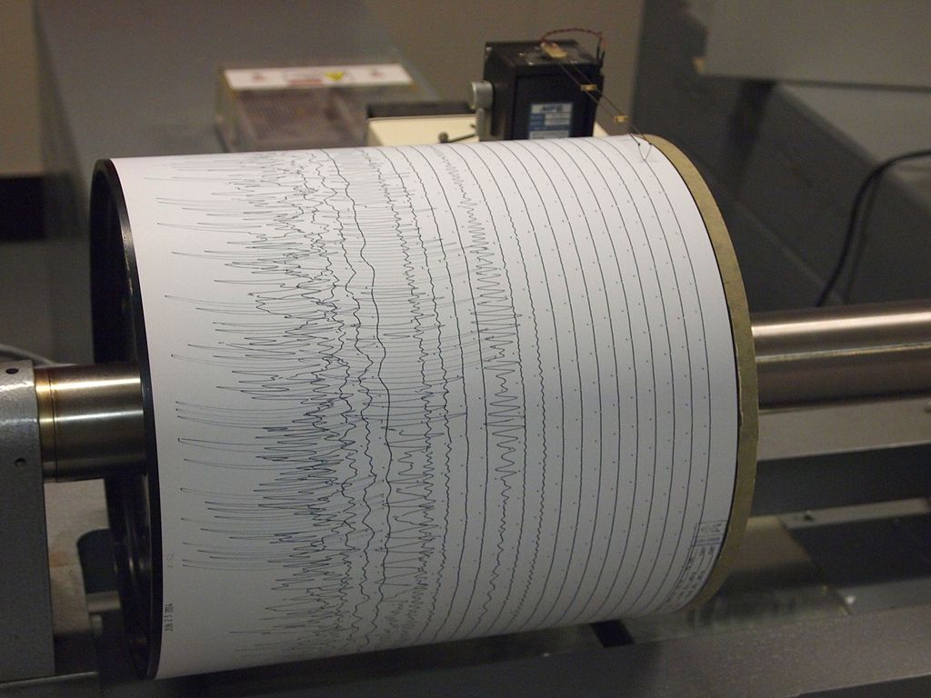 Example of an analog seismogram registration using a helicorder drum (source: <a href='https://en.wikipedia.org/wiki/File:Seismogram_at_Weston_Observatory.JPG' target='_blank'>wikipedia</a>).